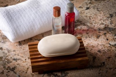 teak soap dish with shampoo bottles and towel
